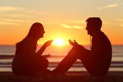 Amigos o pares de las adolescencias que hablan en la puesta del sol Imágenes de archivo libres de regalías