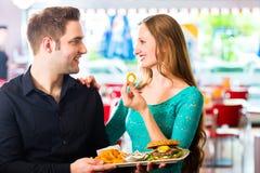 Amigos o pares que comen los alimentos de preparación rápida con la hamburguesa y las fritadas Imagen de archivo libre de regalías