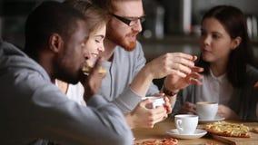 Amigos ou colegas multinacionais que comem o café ou o chá bebendo da pizza video estoque