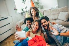 Amigos ou equipe feliz com os acessórios do partido que tomam o selfie fotografia de stock royalty free