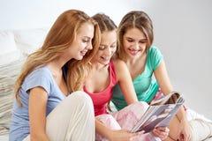 Amigos ou meninas adolescentes que leem o compartimento em casa Foto de Stock