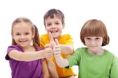 Amigos para sempre - os miúdos que mostram os polegares levantam sinais Fotografia de Stock