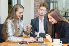 Amigos pensativos jovenes que tienen una competencia del ajedrez en un fondo del café Concepto de la amistad Foto de archivo
