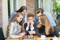 Amigos pensativos jovenes que tienen una competencia del ajedrez en un fondo del café Concepto de la amistad Imagen de archivo