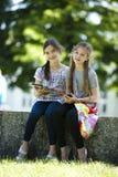 Amigos pequenos com tabuleta do PC e o telefone móvel Fotografia de Stock