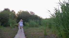 Amigos pequenos felizes menina e atualização e corrida do jogo do menino na ponte de madeira na natureza entre a vegetação verde vídeos de arquivo