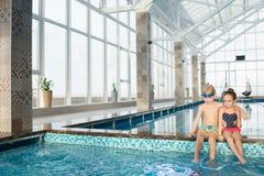Amigos pequenos que balançam os pés na piscina imagens de stock