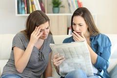 Amigos preocupados que leem notícias do jornal fotografia de stock