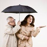 Amigos preocupantes en impermeables bajo el paraguas imagenes de archivo