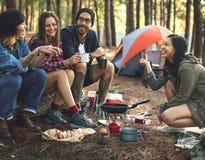 Amigos que acampam comendo o conceito do alimento imagens de stock