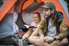 Amigos que acampan en el bosque junto foto de archivo