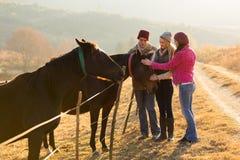 Amigos que acarician caballos Foto de archivo