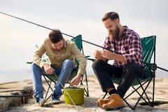 Amigos que ajustan las cañas de pescar con cebo en el embarcadero foto de archivo libre de regalías