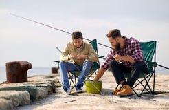 Amigos que ajustan las cañas de pescar con cebo en el embarcadero imagen de archivo