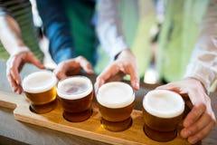Amigos que alcançam para o demonstrador da cerveja no contador fotos de stock royalty free