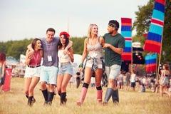 Amigos que andam através de um local do festival de música Fotos de Stock Royalty Free