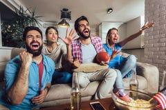 Amigos que animan a la liga del deporte junto en la TV y que celebran la victoria en casa imagen de archivo