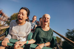 Amigos que animan y que montan la montaña rusa en el parque de atracciones Imagenes de archivo