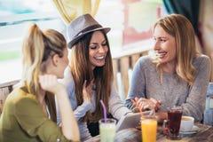 Amigos que apreciam na conversação e no café bebendo em c imagens de stock