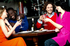 Amigos que apreciam o comensal em um restaurante Fotografia de Stock Royalty Free