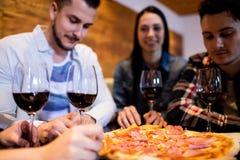 Amigos que apreciam a pizza e o vinho imagem de stock royalty free