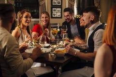 Amigos que apreciam uma refeição Fotografia de Stock