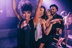 Amigos que bailan en club de noche Foto de archivo