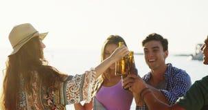 Amigos que bailan mientras que comiendo cerveza en la playa 4k almacen de metraje de vídeo