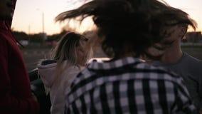 Amigos que bailan teniendo en cuenta puesta del sol concepto de las vacaciones de verano, del viaje por carretera, de las vacacio almacen de video