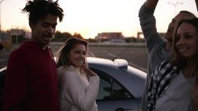 Amigos que bailan teniendo en cuenta puesta del sol concepto de las vacaciones de verano, del viaje por carretera, de las vacacio almacen de metraje de vídeo