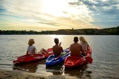 Amigos que baten los kajaks en el río o el lago hermoso debajo del cielo dramático de la tarde en la puesta del sol Fotografía de archivo