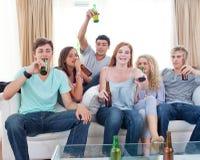 Amigos que bebem a cerveja em casa e que prestam atenção à tevê Imagens de Stock