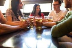Amigos que bebem a cerveja na barra ou no bar Fotos de Stock Royalty Free