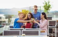 Amigos que bebem os cocktail exteriores em um balcão da sótão de luxo foto de stock royalty free