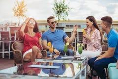 Amigos que bebem os cocktail exteriores em um balcão da sótão de luxo imagem de stock royalty free