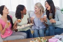Amigos que beben el vino blanco y que comparten las magdalenas en el partido Imagen de archivo