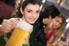 Amigos que beben la cerveza en barra Foto de archivo libre de regalías