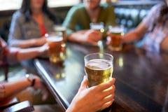 Amigos que beben la cerveza en la barra o el pub Imágenes de archivo libres de regalías