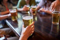 Amigos que beben la cerveza en la barra o el pub Fotos de archivo libres de regalías