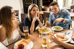 Amigos que beben la cerveza en un restaurante Imagen de archivo libre de regalías