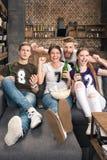 Amigos que beben la cerveza y que comen las palomitas Fotos de archivo libres de regalías