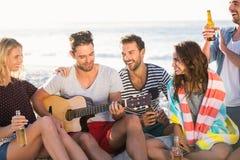 Amigos que beben la cerveza y que tocan la guitarra Fotos de archivo libres de regalías