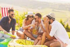 Amigos que beben los cócteles en un partido del poolside imagenes de archivo
