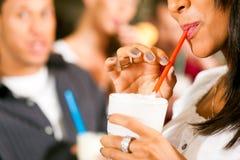 Amigos que beben los milkshakes en una barra foto de archivo