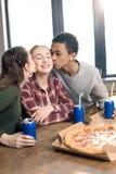 Amigos que besan las mejillas sonrientes del ` s del adolescente, comiendo concepto de la pizza en casa Imagen de archivo libre de regalías