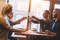 Amigos que brindam em um restaurante, comemorando imagem de stock