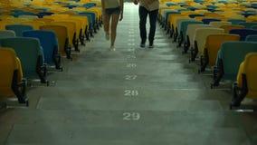 Amigos que caminan arriba en el estadio, buscando asientos, evento en la arena deportiva metrajes