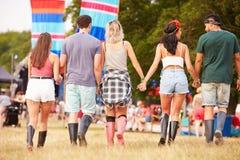 Amigos que caminan junto en un sitio del festival de música, visión trasera imagenes de archivo