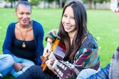 Amigos que cantan canciones en el parque que se divierte juntas Imágenes de archivo libres de regalías