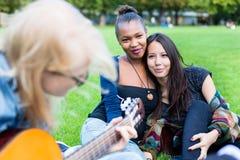Amigos que cantan canciones en el parque que se divierte juntas Fotos de archivo